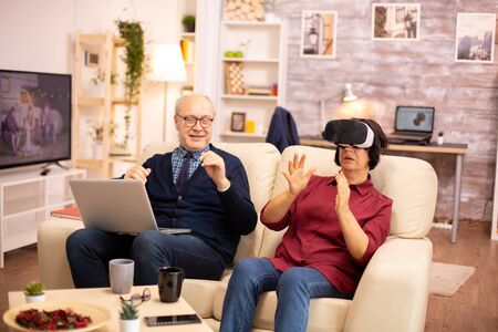 Old elderly retired woman in her 60s experiencing virtual reality for the first time in their cozy apartment