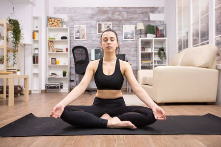 Beautiful adult woman relaxing at home doing yoga lotus pose on the mat.
