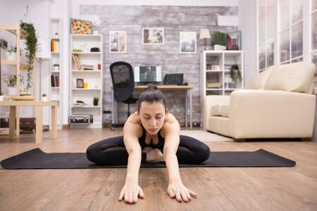 Adult woman with eyes closed sitting in lotus yoga pose relaxing her back and stretching forward.