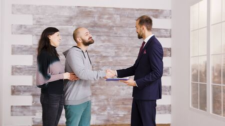 Real estate agent in business suit giving keys to young couple after signing document