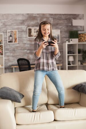 Little girl playing games on smartphones jumping on the couch in living room.
