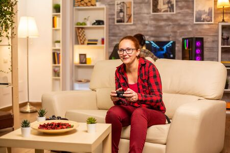 Woman gamer playing video games on the console in the living room late at night Stockfoto