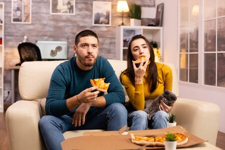 Gorgeous young couple eating pizza while watching TV in the living room sitting on the sofa Stockfoto