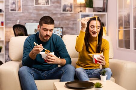 In modern cozy living room couple is enjoying takeaway noodles while watching TV comfortably on the sofa Stockfoto