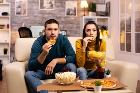Beautiful young couple watching TV and eating fast food takeaway in the living room