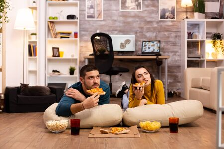 Couple sitting on the floor and watching TV in their living room.