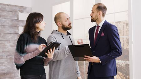 Real estate agent talking with couple and holding documents home owning contract in new apartment.