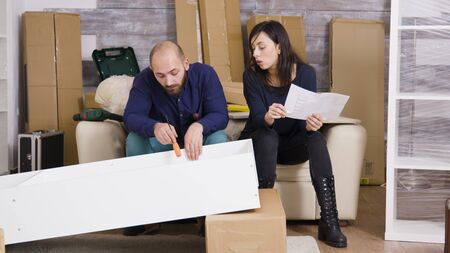 Young couple assembling a shelf as a team in their new apartment and reading instructions.