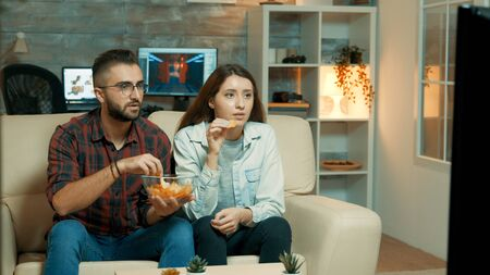 Young couple sitting on the couch and watching television enjoying their chips. Couple looking tense on television. Stockfoto