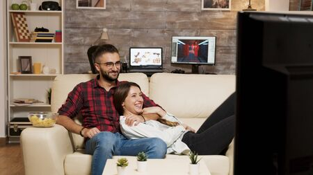 Attractive young couple relaxing on couch while watching a movie on television.
