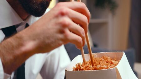 Close up of tired entrepreneur eating noodles with chopsticks in living room while watching tv.