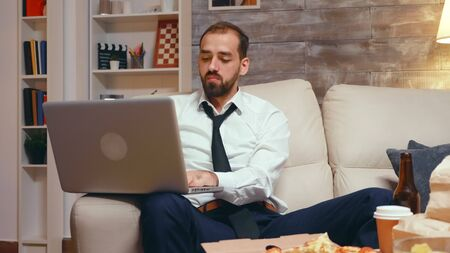 Tired businessman in living room working on laptop and eating pizza. Entrepreneur wearing a tie. Stockfoto