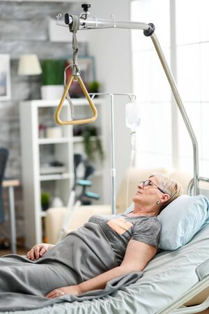 Retired old woman lying peacefully in a nursing home bed. Aged granny in nursing home.