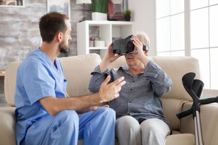 Senior woman in nursing amased while using vr glasses. Young doctor and elderly age woman.