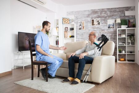 Male nurse on a chair in a nursing home talking with elderly age man while he is sitting on couch. Stock Photo