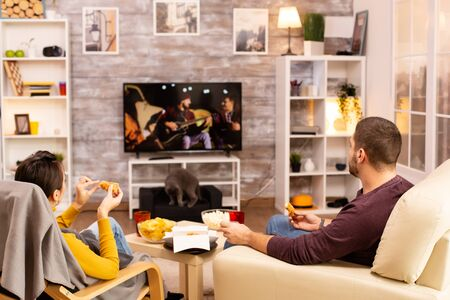 Back view of couple in living room watching a movie on the TV while eating takeaway food Stockfoto
