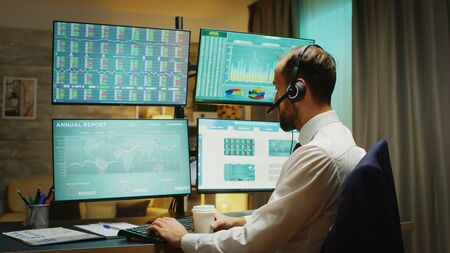Businessman in home office drinking coffee and talking on headphones about financial crisis. Four big displays with different stock market data