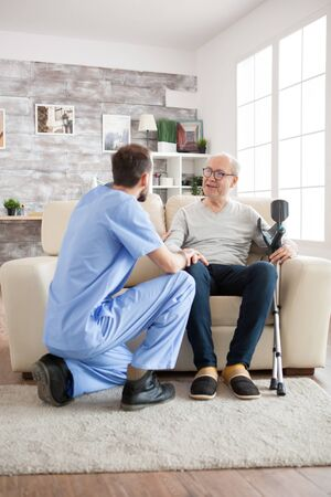 Old man with mental health recognise his doctor in nursing home. Caretaker talking with old man. Stock Photo