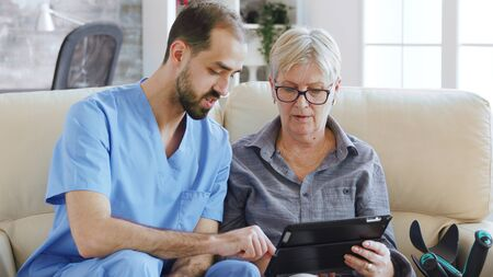 Male assistant teaching senior retired elderly old woman how to use her tablet computer in nursing home for her therapy