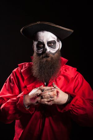 Man dressed up like a dangerous pirate for halloween over black background. Stock Photo