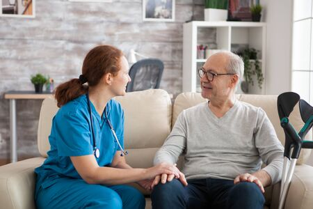Female doctor with stethoscope in nursing home talking with old patient. Stock Photo
