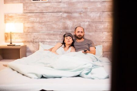 Caucasian husband and wife wearing pajamas while watching tv before bedtime.