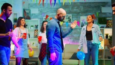 Attractive bald young man doing robot dance moves while partying with his friends in a room full of neon lights, disco ball and cool vibes