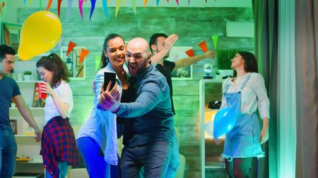 Cheerful bald man taking a selfie with his attractive friend at the party. Using smartphone.