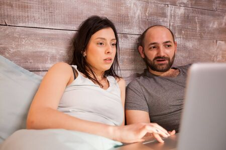 Young caucasian couple wearing pajamas surfing on the internet using laptop.