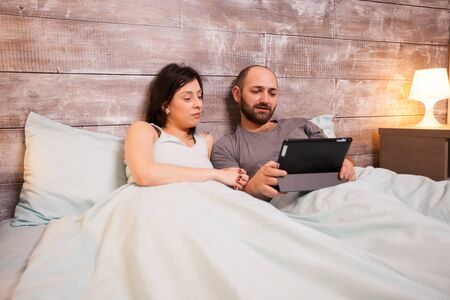 Caucasian couple wearing pajamas layibng in bed using tablet computer.