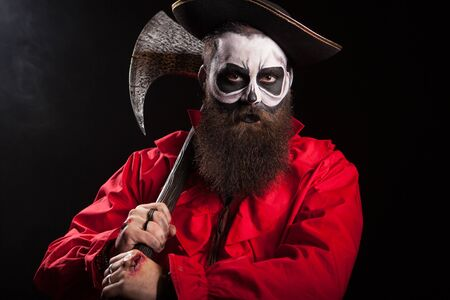 Medieval captain holding an axe over black background. Halloween outfit.
