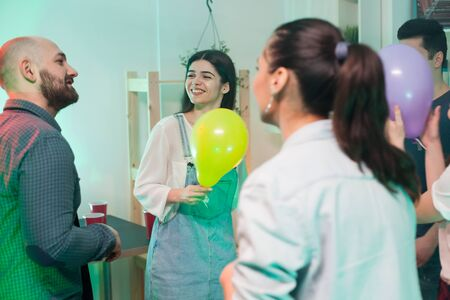 Young woman with a balloon smiling at attractive male at a party.