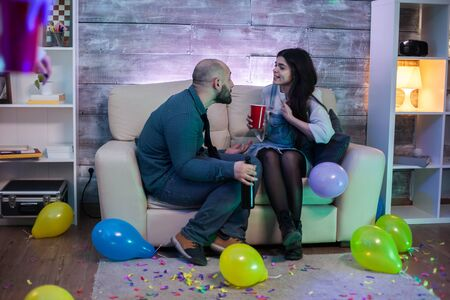 Young couple having an argument sitting on the couch at their friends party.