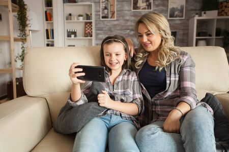 Little girl with braces and her mother on a lazy weekend using smartphone sitting on the couch. Фото со стока - 147269486