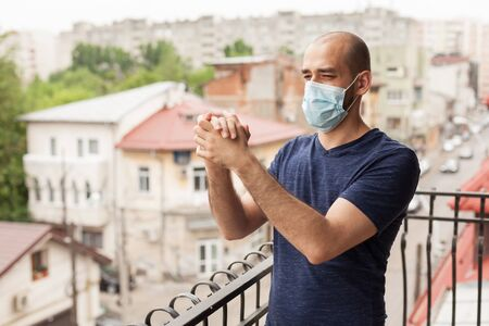 Happy man clapping on balcony in support of doctors fighting coronavirus.
