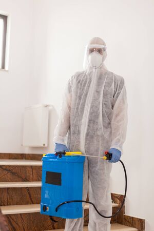 Scientist in coverall suit spreading disinfectant against coronavirus in office building.