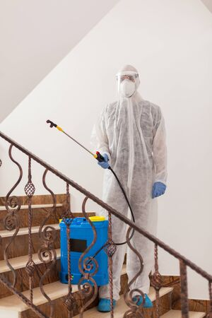 Specialist in hazmat suit spreading antibacterial in office building.