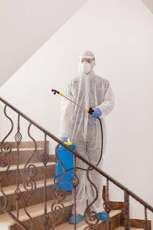 Man in protective suit disinfecting building against coronavirus contamination.