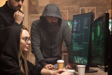 Bearded hacker wearing a hoodie while his team breaks vulnerable government servers.