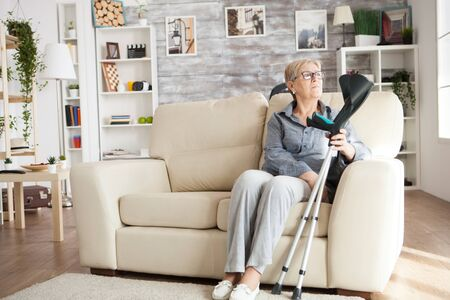 Lonely old woman sitting on couch in a nursing home holding crutches and looking through the window.