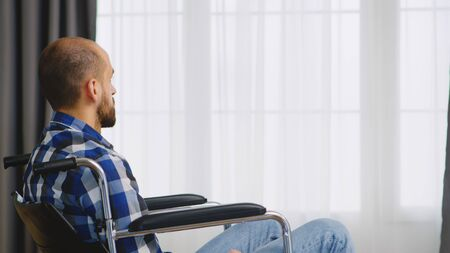 Paralyzed young man sitting on wheelchair in living room.