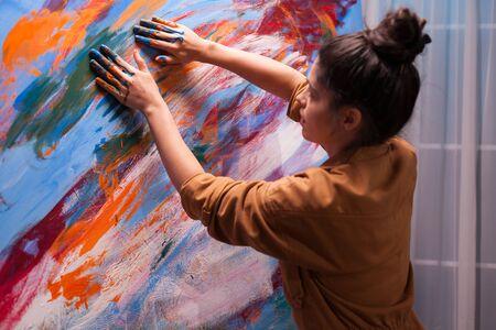 Using fingers on canvas as brush in art studio.