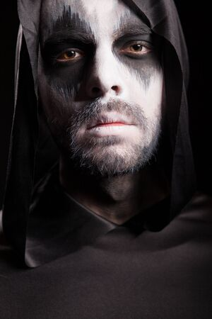Close up portrait of grim reaper isolated over black background. Halloween costume.