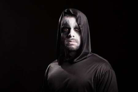Young man looking serious into the camera dressed up like grim reaper. Halloween costume. Archivio Fotografico