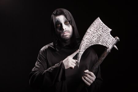 Dangerous scary man dressed up like grim reaper with an axe over black background. Archivio Fotografico