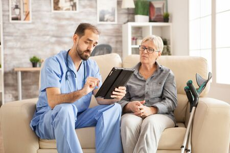 Doctor in nursing home using tablet computer while taking with female pensioner.
