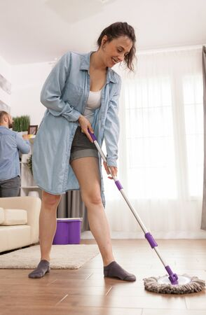 Young wife laughing while mopping the floor.