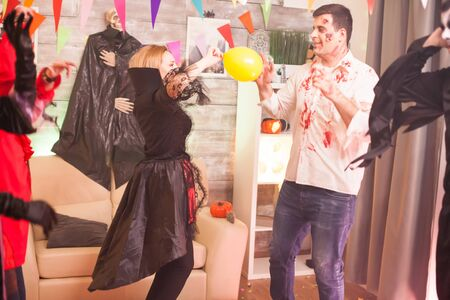 Bloody zombie playing with a balloon while celebrating halloween with his friends.