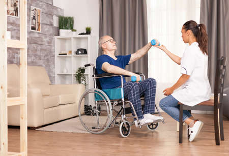 Senior man with muscle trauma recovering after the accident. Disabled handicapped old person with social worker in recovery support therapy physiotherapy healthcare system nursing retirement home. Imagens