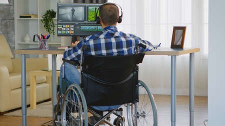 Disabled video editor sitting on wheelchair doing post production on film. Banco de Imagens